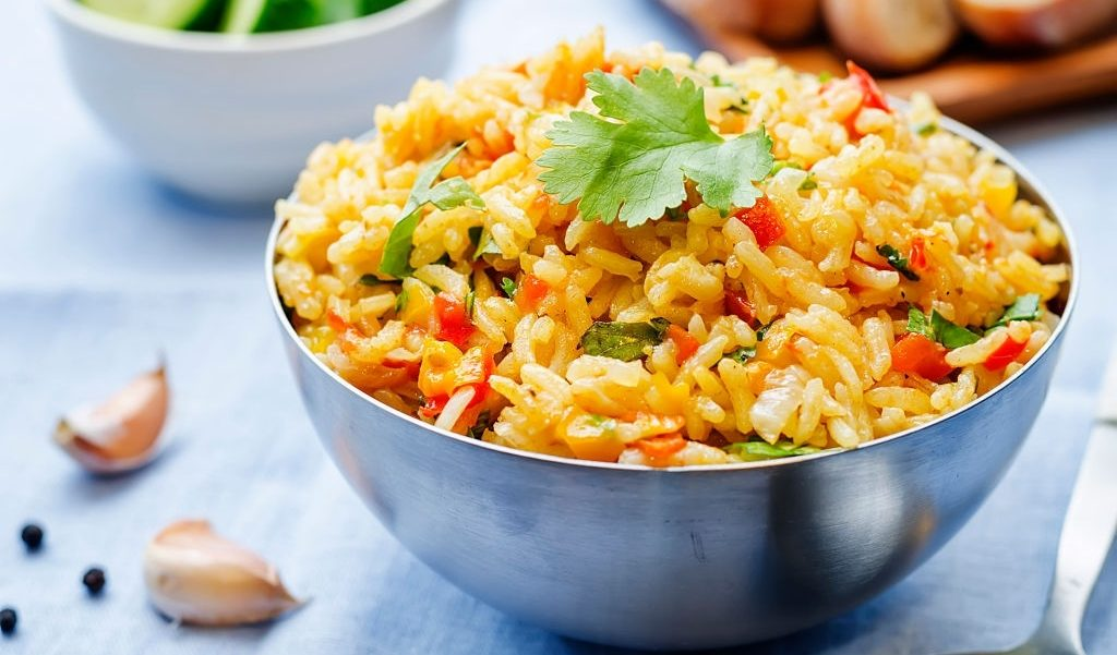 saffron rice with vegetables and cilantro on a blue background. the toning. selective focus