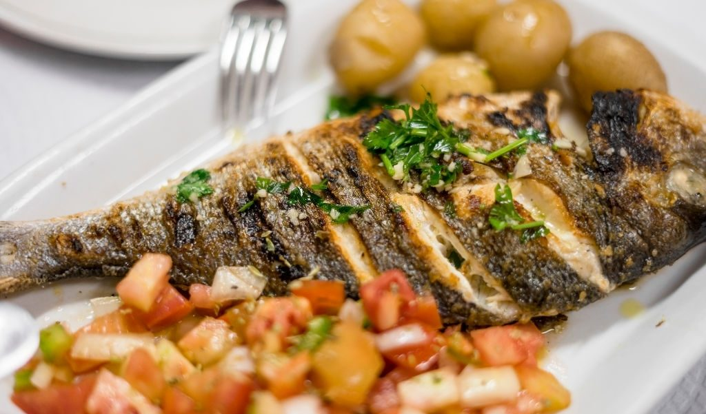 Traditional portuguese grilled golden fish served with potatoes and tomato salad